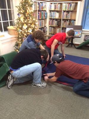 Teen boys prep fleece for blankets at Project Linus at the Pawling Library.