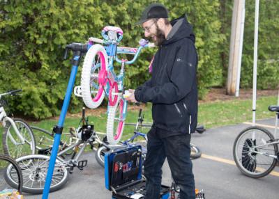 a bike mechanic from dream bikes fixes a girl's bike.